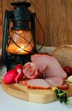 Still life with ham, homemade bread and a lantern Royalty Free Stock Images