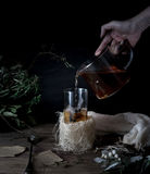 Still life. hands pour tea in transparent cup. dark background, vintage Royalty Free Stock Image