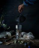 Still life. hands pour tea in transparent cup. dark background, vintage Stock Photos