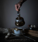 Still life. hands pour tea in transparent cup. dark background, vintage Stock Photography