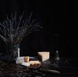 Still life. hard cheese, bunch of lavender, antique knife on wooden table. black background Royalty Free Stock Image