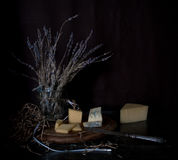 Still life. hard cheese, a bunch of lavender, antique silver knife on  wooden table. black background Stock Images