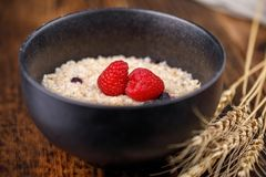 Still life of a healthy breakfast. Oatmeal with blueberries and fresh raspberries on a wooden background. Close-up Royalty Free Stock Images