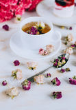 Still life with herbal tea, cake and roses Stock Image