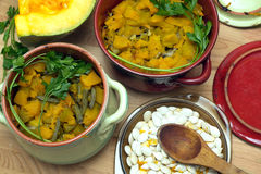 Still-life with homemade fried pumpkin with carrot and green beans in color clay pots Stock Images