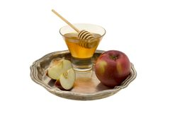Still-life with honey and an apple. Small still-life  with honey and an apple on a brilliant metal tray Royalty Free Stock Photography