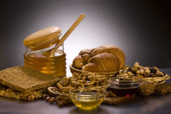 Still life with honey, nuts, bread, bun. Stock Photography