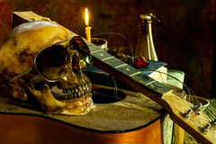 Still life with human skull bespectacled on guitar. Background Stock Photo