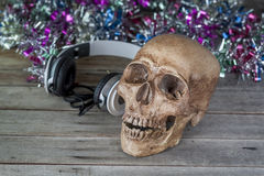 Still life.Human skull headphones on the old wooden floor Stock Photography