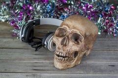 Still life.Human skull headphones on the old wooden floor Stock Photography