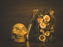 Still life with human skull and dry flowers. Still life with human skull and knife and dry flowers, Vintage style stock image