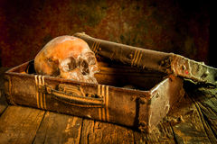 Still life with a human skull with old treasure chest and gold, diamond and jewelry. On wooden background stock photography