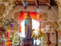 Still life, idyll in a small chapel in the mountains from sthe south of Tenerife. Candlesticks, Christ figure, colorful reflections of light from the window royalty free stock photos