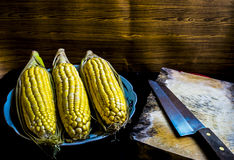 Still Life image of corncob and a knife on wooden chopping board Stock Photos