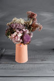 Still life image of dried flowers in rustic vase against weathered wooden background Royalty Free Stock Image