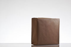 Parcels wrapped up in brown papper. Still life image of small parcels wrapped up in brown paper shot on a white background in the studio stock photo