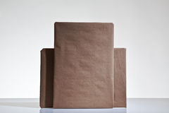Parcels wrapped up in brown papper. Still life image of small parcels wrapped up in brown paper shot on a white background in the studio royalty free stock image