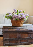 Still life interior details, bouquet of lilac in basket on trunk Royalty Free Stock Image