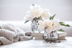 Still life home cosiness. Still life with interior details and flowers with peonies in the living room, the concept of home comfort and interior royalty free stock photography