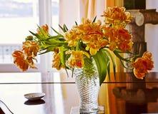Still life interior, elegant glass vase with orange tulips. Romantic yellow orange tulips in glass in a room interior Stock Image