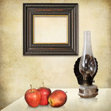 Still life, interior with empty frame. Retro still life, an art deco empty frame, three red apples, an old oil lamp on a grunge textured interior stock photography