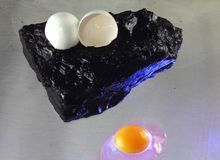 Still life. Irrationality. Philosophy. Nonsense. The philosophy of stupidity. Annoying easy.The solid stone. The egg is fragile Stock Photo