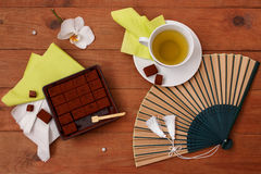 Still life with Japanese chocolate, green tea, and a fan on a wo. Still life with Japanese black chocolate, green tea, and a fan on a wooden table Royalty Free Stock Photography