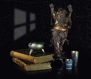 Still life with the Japanese sculpture. A retro books and shot glasses Stock Photos