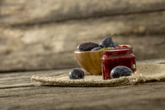 Still life with a jar of home made plum marmelade and wooden bow Royalty Free Stock Images