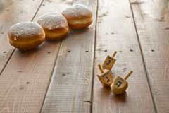 Hanukkah celebration concept-donuts and dreidels on rustic table. Still life for jewish holiday Hanukkah with 3 donuts and 3 dreidels on wooden rustic table royalty free stock photos