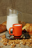 Still life with a jug of milk and croissants. Still life with a jug, a mug of milk and croissants Stock Photography