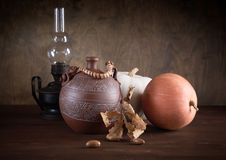 Still-life with a jug an oil lamp and pumpkins. On a table Stock Photos