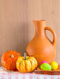 Still life with jug, pumpkins and Easter eggs. At the checkered tablecloths royalty free stock photos