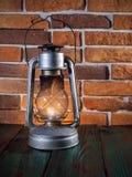 Still life kerosene lamp shines on  wooden desktop  stone brick background. Still life kerosene lamp shines on  wooden desktop  stone brick background Stock Photo