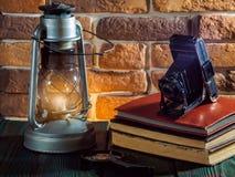 Still life kerosene lamp shines on wooden desktop stone brick background book camera. stock photo