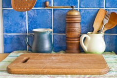 Still life with kitchen accessories. Green jug, hand grinder, vintage wooden spoons, cutting board on napkin. Blue tile Royalty Free Stock Photos