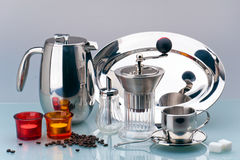 Still life of kitchen items. Chrome-plated coffee pot, coffee grinder, dishes, salt cellars and coffee cup stock photos
