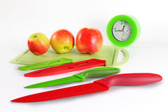 Still life with kitchen knives. Still life with kitchen accessories against the background of apples and hours Royalty Free Stock Photo