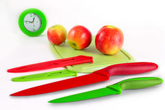 Still life with kitchen knives. Still life with kitchen accessories against the background of apples and hours Royalty Free Stock Photography