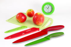 Still life with kitchen knives. Still life with kitchen accessories against the background of apples and hours Stock Photography