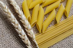 Still life for a kitchen of wheat ears and pasta from wheat on a sackcloth background Made in Kazakhstan royalty free stock photo