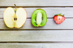 Still life with a kiwi, apple and strawberry on a wooden table Royalty Free Stock Image