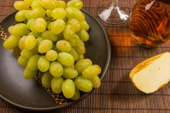 Large brush of green grapes in a ceramic plate, a decanter and a glass of wine and cheese. Still life - a large brush of green grapes in a ceramic plate, a royalty free stock photo