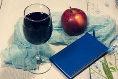 Still-life. red Apple, blue notebook, glass of wine and turquoise fabric on light background royalty free stock photo