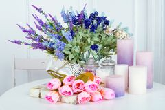 Still life of lavender flower tulips, candles and a book. On light background Royalty Free Stock Images