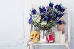 Still life of lavender flowers in a watering can with candles and sculp on a white chair Stock Photos