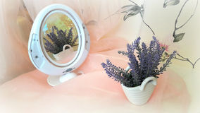 Still life: lavender in the mirror. Beautiful interior arrangement: bouquet of lavender in a white porcelain basket reflected in the oval mirror on the pink Stock Image
