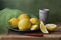Still life with lemons and green gauze. Still life with lemons, green gauze and cup on wooden table Royalty Free Stock Photography