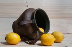 Some lemons and an old copper amphora. Still life with lemons and old copper amphora Royalty Free Stock Photography