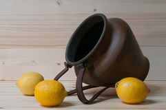 Some lemons and an old copper amphora. Still life with lemons and old copper amphora Royalty Free Stock Photo